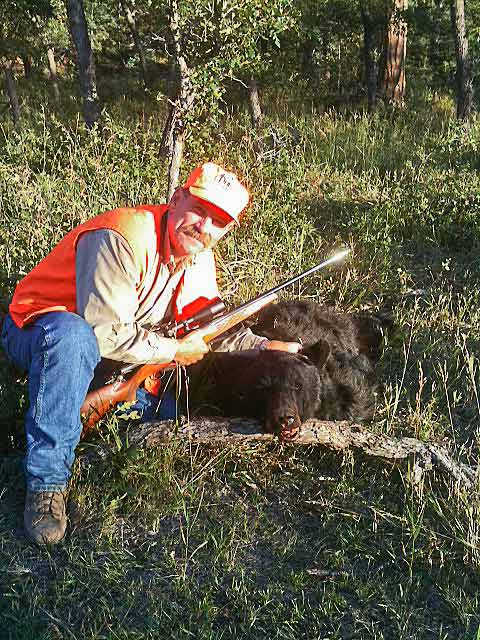 Happy hunter with a black bear harvested on the ranch.
