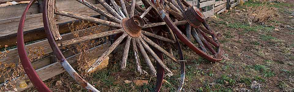 Old wagon wheels lean against a fence